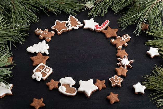 黒の背景とトウヒの枝に円の形でジンジャーブレッドクッキー。スペースをコピーします。