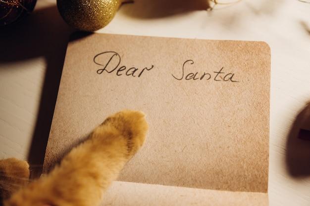 Рыжий кот пишет письмо деду морозу на столе с рождественской гирляндой. скопируйте пространство. новый год. рождество