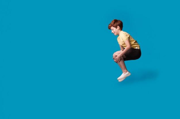 Рыжий кавказский мальчик, улыбаясь и продвигая что-то в синей студии, прыгает в бассейне