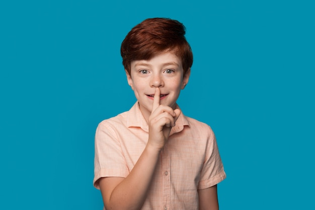 Ginger caucasian boy is gesturing the silence soung smiling on a blue studio wall in casual clothes