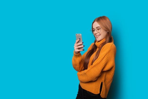 そばかすとメガネの生姜白人の女の子が空白の青い壁で誰かとおしゃべりしています