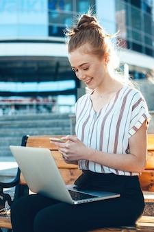 そばかすのある生姜白人女性は、外のベンチに座っている間、電話とコンピューターを使用しています