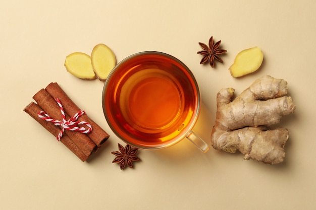 Ginger, cinnamon and cup of tea on beige background