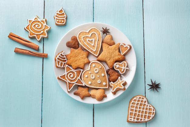 Ginger cookies decorated with icing on a plate on a blue wooden background.