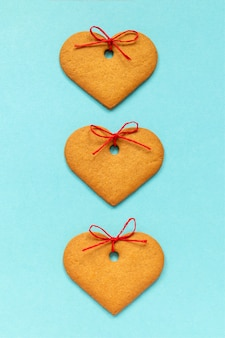 Ginger cookies heart-shaped decorated with a bow on blue background