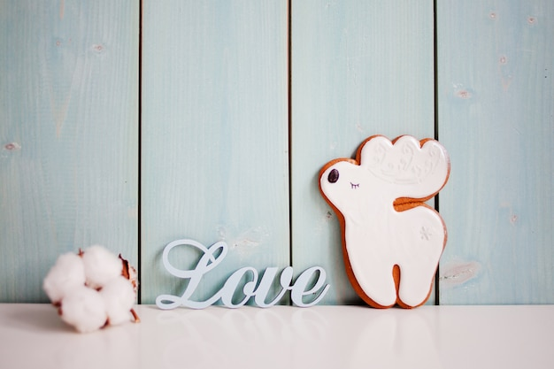 Ginger cookies-reindeer. delicate turquoise background with cotton and inscription love