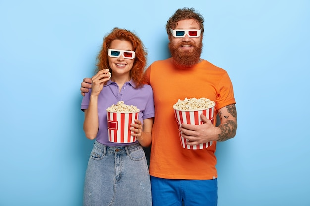 Ginger couple posing with popcorn and glasses
