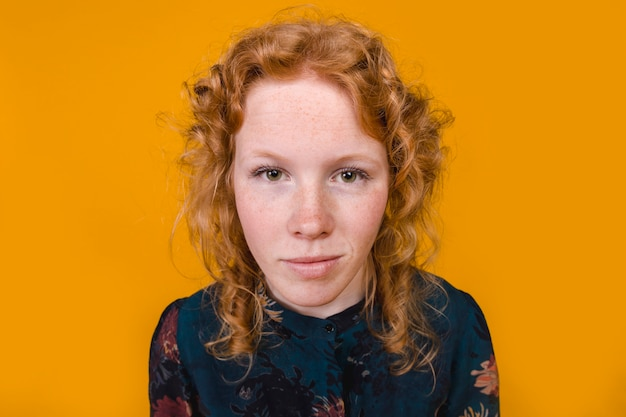 Ginger curly young woman looking at camera