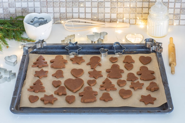 Ginger dough, festoon, spruce branches, baking tins and a rolling pin are put on the baking sheet