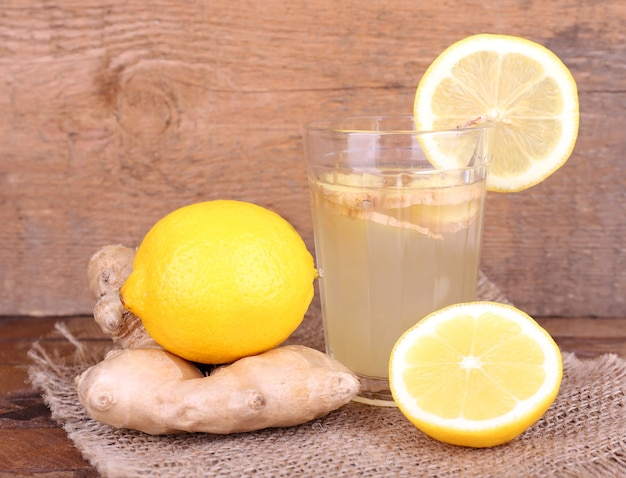 Ginger drink and ginger root and lemon on sackcloth napkin on wooden table on wooden table