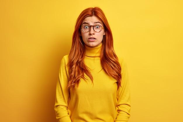 생강 유럽 여성은 캐주얼 터틀넥을 착용하고 흥분된 느낌을 놀라게 응시합니다.