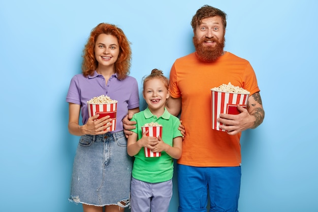 Ginger family spend free time in cinema, watch funny movie, smile happily, eat delicious popcorn, stand closely to each other, enjoy togetherness, entertain themselves. leisure, family time concept