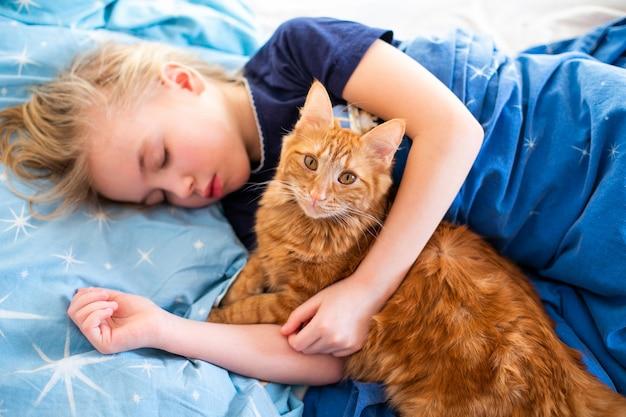 파란 침대에 잠자는 소녀와 생강 솜 털 고양이