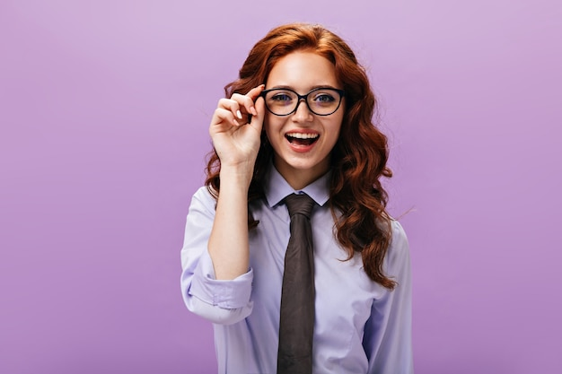 Ginger girl in eyeglasses looks into camera on purple wall