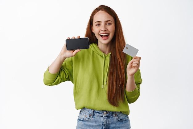La ragazza zenzero acquista, paga in internet, mostra la carta di credito e lo schermo orizzontale dello smartphone su bianco