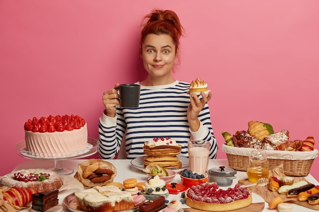 Ginger girl sits at festive table overloaded with many sweet desserts, eats yummy fresh baked cake and drinks tea, has unhealthy but tasty lunch, feels hungry, being voluptuous.