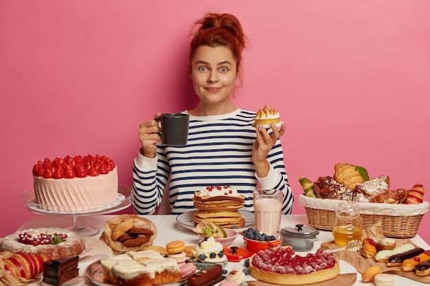 La ragazza dello zenzero si siede a un tavolo festivo sovraccaricato di molti dessert dolci, mangia una deliziosa torta appena sfornata e beve tè, ha un pranzo malsano ma gustoso, ha fame, è voluttuosa.