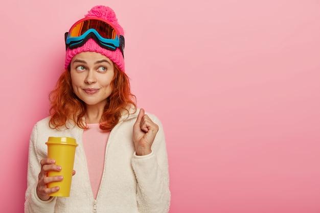 Ginger girl sciatore gode di località invernale, ha una pausa caffè dopo aver raggiunto la cima della montagna, applausi il sogno che si avvera, indossa occhiali da snowboard, vestiti caldi,