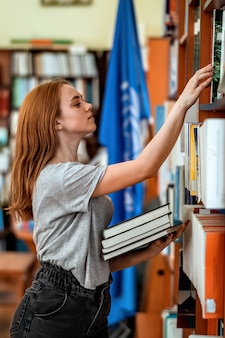 Ginger girl with casual clothes searching for old books