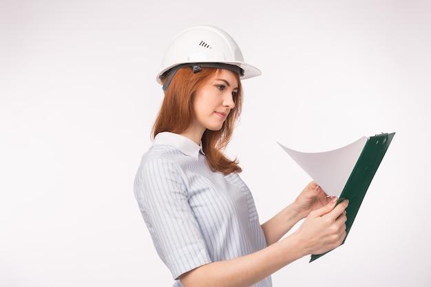 Рыжая девушка в шлеме с планшетом.