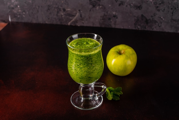 Ginger green apple smoothie on concrete background.