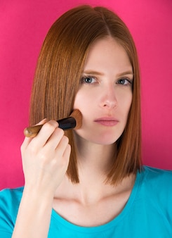 Ginger hair young woman using make up brush
