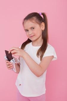 Ginger half-naked joyful girl smiling and eating chocolate isolated over pink wall.