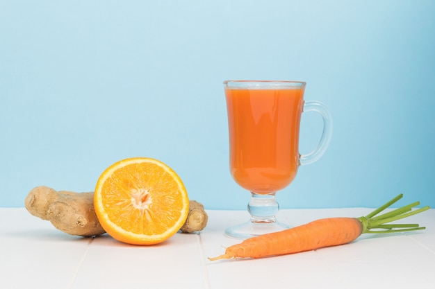 Ginger, half an orange, carrots and a glass glass with a smoothie on a white table. the concept of healthy eating.