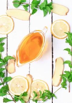 집에서 만든 레모네이드 소박한 스타일의 흰색 나무 배경 재료에 생강 꿀 레몬 민트...