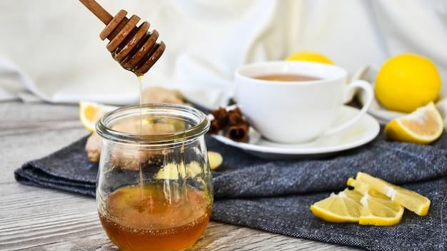 생강 뜨거운 면역 강화 비타민 천연 음료 감귤류, 꿀, 재료를 나무 배경에 소박한 스타일로 넣은 것입니다. 카모마일 차. 건강한 개념