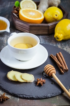 Ginger hot  immunity boosting vitamin natural drink with citrus, honey and cinnamon and ingredients