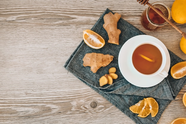 Ginger hot immunity boosting vitamin natural drink with citrus, honey and ingredients in a rustic style on wooden background. chamomile tea. healthy concept