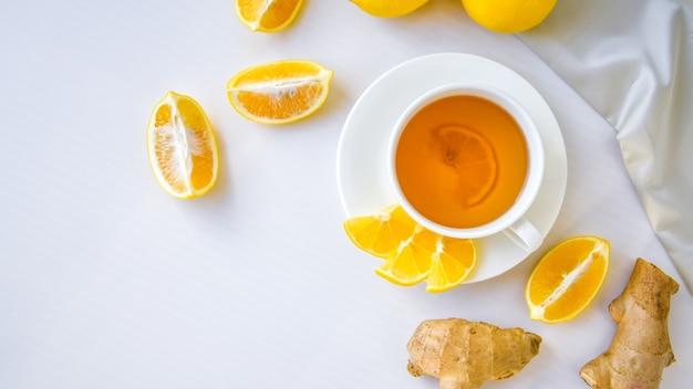 Имбирь горячий, повышающий иммунитет напиток витаминный натуральный с цитрусовым лимоном в деревенском стиле на белом фоне. ромашковый чай. здоровая концепция копией пространства