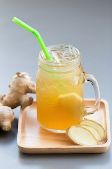 Ginger juice with sugar on gray table. Premium Photo