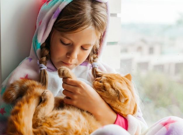 生姜の子猫と小さな女の子が窓辺に座って窓の外を見ています。