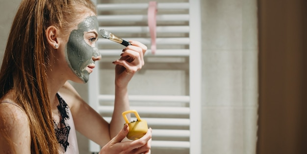 Ginger lady in front of the mirror applying a facial mask using special tools