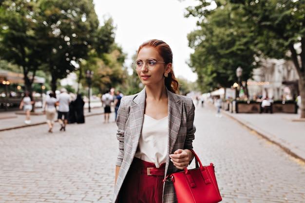 眼鏡の生姜の女性は赤いハンドバッグを保持します
