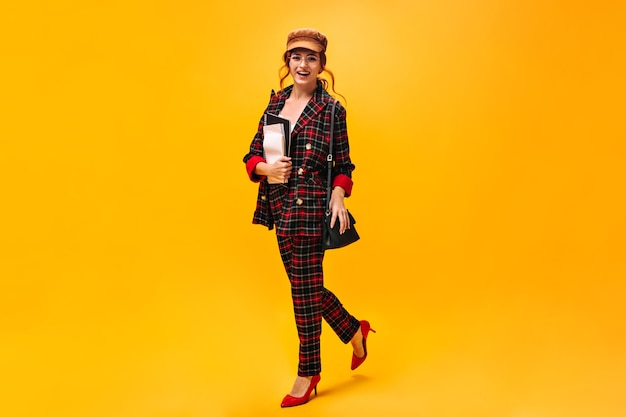 Ginger lady in stylish suit poses with notebooks on orange wall