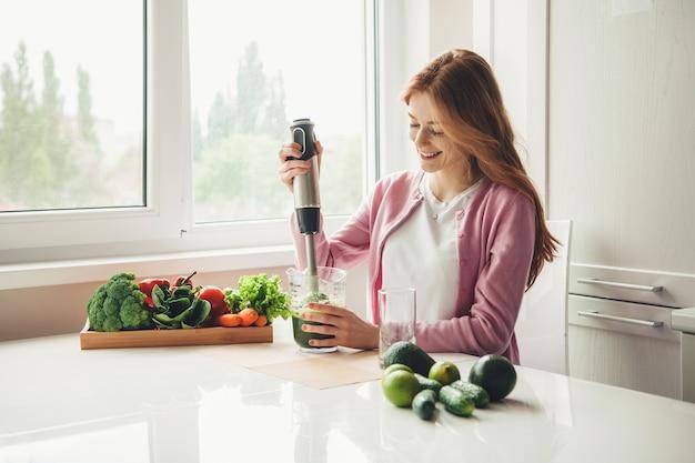 ライムとアボカドからキッチンでフレッシュジュースを作る電気スクイーザーを使用してそばかすのある生姜の女性