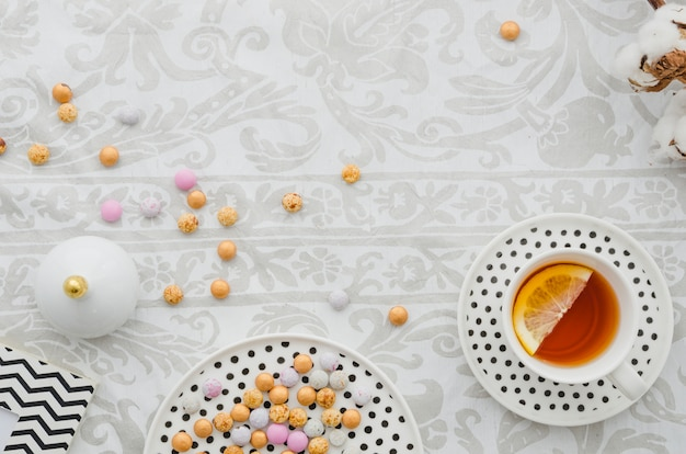 Ginger lemon tea cup and saucer with colorful candies on wallpaper