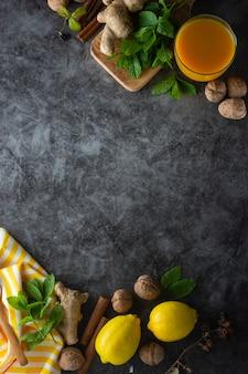 Имбирь, лимоны и листья мяты на темной поверхности,