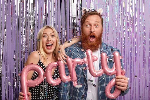 Рыжий мужчина и блондинка на вечеринке, держа воздушные шары