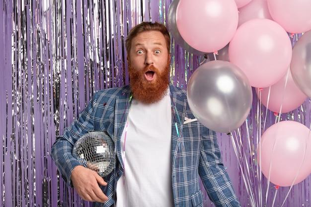 Рыжий человек на вечеринке держит диско-глобус и воздушные шары