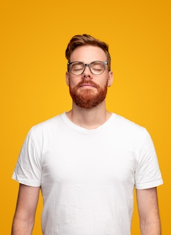 Ginger man in glasses and white t shirt closing eyes and breathing while meditating against yellow background