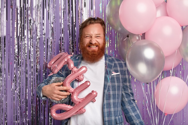 Ginger man at party holding disco globe and balloons
