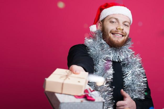 Рыжий человечек с бородой и новогодней шапкой дарит подарок, улыбаясь на красной стене