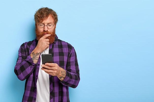 Ginger millennial guy uses cell phone application for synchronizing data, has serious look, wears round spectacles