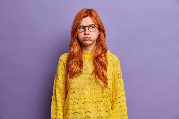 Ginger offended young woman blows cheeks and makes unhappy grimace holds air has moody expression wears yellow sweater displeased with awful situation happened shows bad character