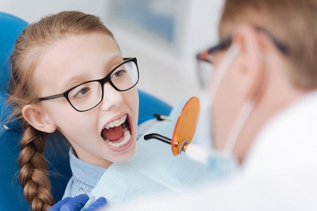 생강 긍정적 인 아가씨가 치과 의사를 방문하고 특수 의자에 앉아 치아를 치료하고 미백하는 동안
