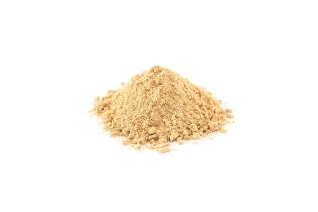 白いテーブルで分離された生姜の粉。